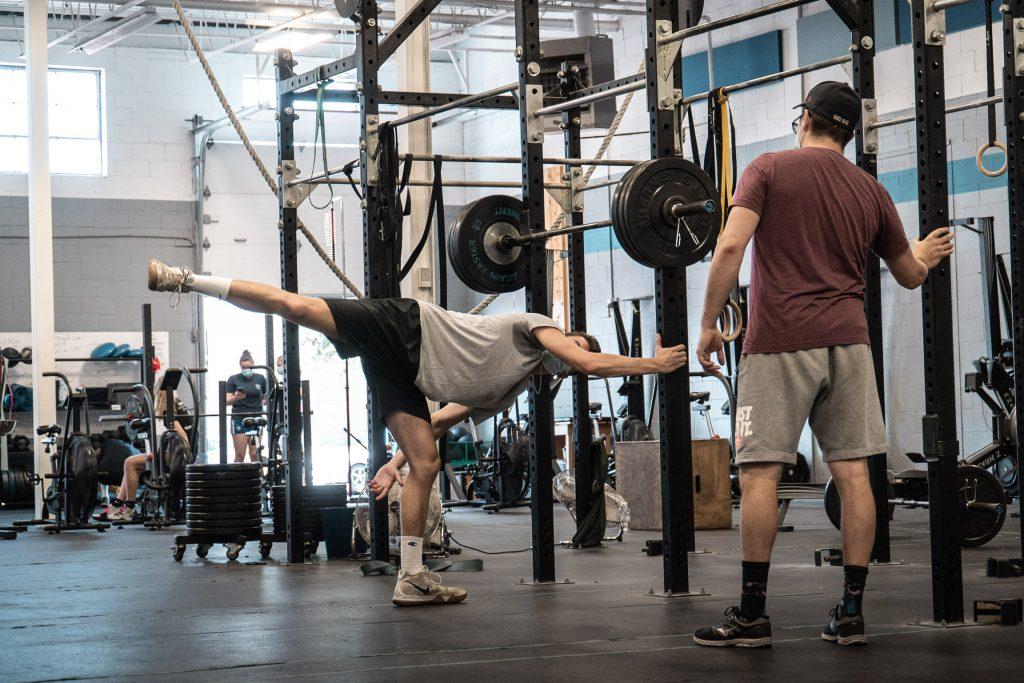 Un athlète effectue un mouvement d'étirement sous la supervision de son entraineur